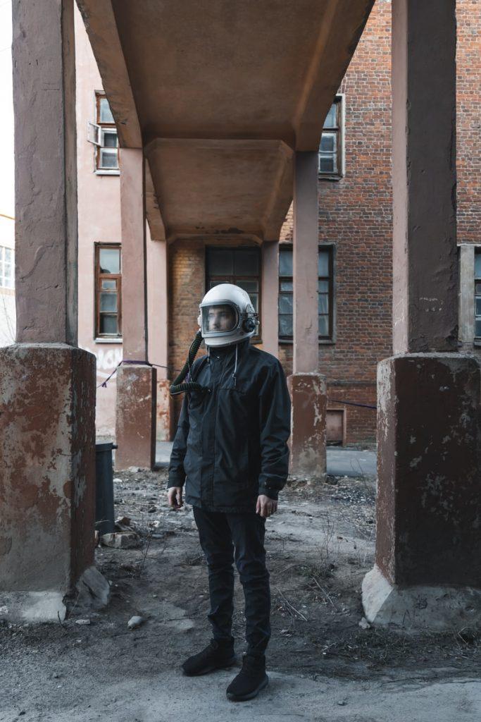 man in black jacket wearing white helmet standing beside brown concrete building during daytime